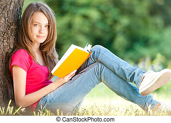 beautiful and happy young student girl sitting on green grass under the tree, smiling and looking into the camera, book in her hands. Summer or spring green park in background
