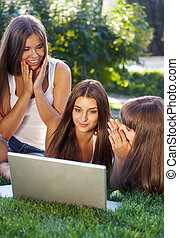 Happy young student girls having fun using a laptop
