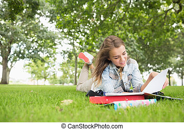 Happy young student studying on the grass on college campus