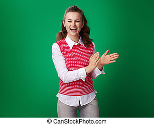 happy young student woman clapping isolated on green background