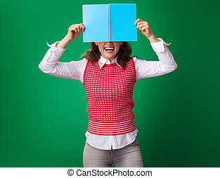 happy young student woman hiding behind blue notebook