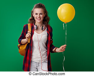 happy young student woman holding yellow balloon