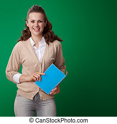 happy young student woman with blue notebook isolated on green