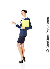 Happy young success business woman pointing on copy space