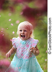 Happy Young Toddler Girl Laughing as Flower Petals Fall Off a Crabapple Tree