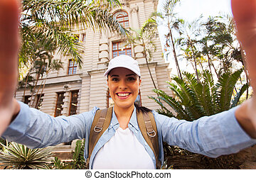 young tourist taking a selfie in front of an old building