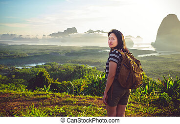 Happy young traveler woman backpacker looking backward to...