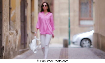 Happy young urban woman in european city. Caucasian tourist...