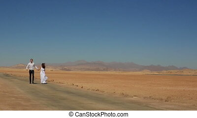 Happy young wedding couple ronning and laughing  in the desert. Honeymoon in Egypt