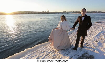 happy young wedding couple walking next to bank of river outdoors