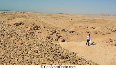 Happy young wedding couple walks in the desert. Honeymoon in Egypt