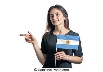 Happy young white woman holding flag Argentina and points to the left isolated on a white background