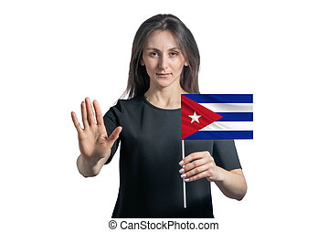 Happy young white woman holding flag of Cuba and with a serious face shows a hand stop sign isolated on a white background