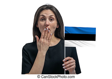 Happy young white woman holding flag of Estonia and covers her mouth with her hand isolated on a white background