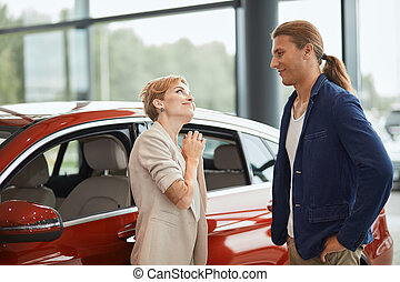 Happy young wife asking to buy a new car for her in the dealership.