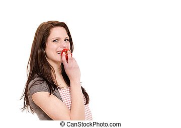 happy young woman about to eat a tomato on white background
