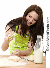 happy young woman adding flour to dough on white background