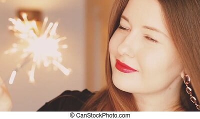 Happy young woman and shiny sparklers, smiling and ...