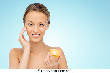 happy young woman applying cream to her face