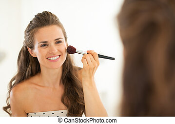 Happy young woman applying makeup in bathroom