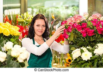 Happy young woman arranging flowers florist shop colorful...
