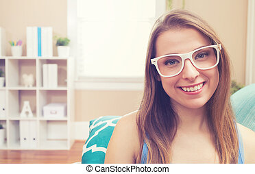 Happy young woman at home on her couch