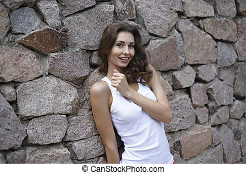 Happy young woman at the wall