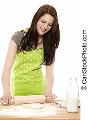 happy young woman baking using rolling pin on dough with white background