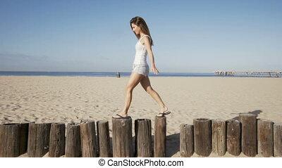 happy young woman balance at wood bollards. summer feeling -...