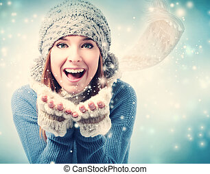 Happy young woman blowing snow