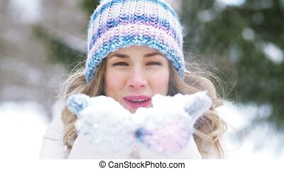 happy young woman blowing to snow in winter forest - people,...