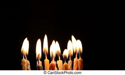 Happy young woman blows out birthday candles, and it gets dark.