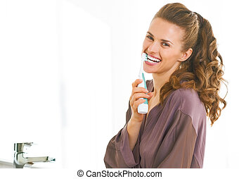 Happy young woman brushing teeth in bathroom