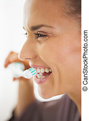 Happy young woman brushing teeth