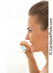 Happy young woman brushing teeth