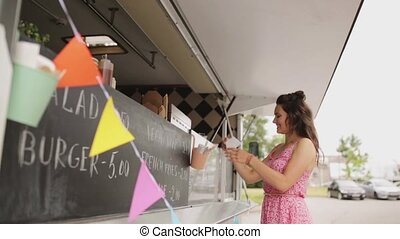 happy young woman buying wok at food truck - street sale,...