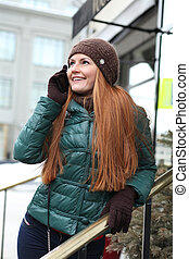 Happy young woman calling by phone