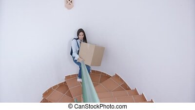 Happy young woman carrying a box upstairs