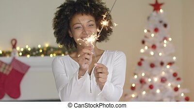 Happy young woman celebrating Christmas at home in front of...