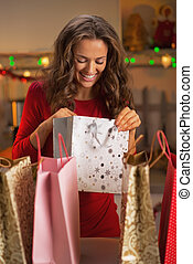 Happy young woman checking bags after christmas shopping