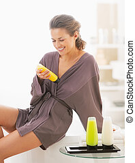 Happy young woman checking bath cosmetics in bathroom