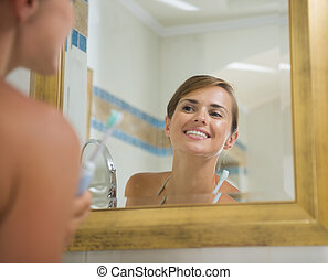 Happy young woman checking teeth after brush