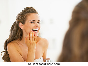 Happy young woman checking teeth in shower teeth in mirror
