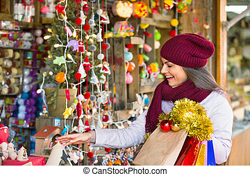 Happy young woman choosing Christmas decoration
