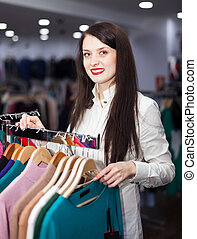 Happy young woman choosing clothes
