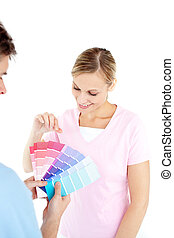 Happy young woman choosing colors for painting a room