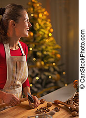 Happy young woman chopping walnuts in christmas decorated kitchen