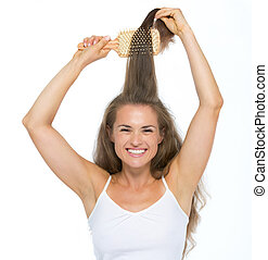 Happy young woman combing hair
