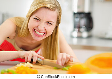Happy young woman cutting fruits in kitchen