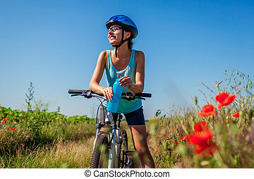 Happy young woman cyclist drinking water and having rest after riding bicycle in summer field.